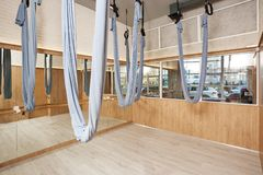 Stretching studio interior with aerial yoga silk hammocks and mirrors. Stretching studio interior with aerial yoga silk hammocks, brick walls and mirrors royalty free stock photo