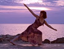 Stretching at sunset. Young woman stretching wearing long dress, sunset at the background stock photos