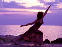 Stretching at sunset. Young woman stretching, sunset at the background Stock Images