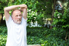 Stretching triceps. Closeup portrait, senior mature man in white shirt, stretching arms, isolated green trees background. Warming up Royalty Free Stock Photography
