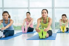 Stretching. Vietnamese pretty girl stretching on mats in fitness studio Royalty Free Stock Photos