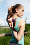 Stretching and warming up. Attractive young sportswoman stretching and warming up Royalty Free Stock Images