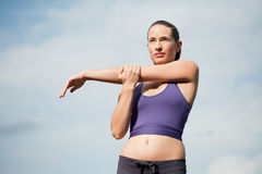 Stretching and warming up. Attractive young sportswoman stretching and warming up Stock Image