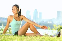 Stretching woman in outdoor exercise. Smiling happy doing yoga stretches after running. Beautiful happy smiling sport fitness model outside on summer / spring stock images