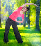 Stretching woman in outdoor sport exercise. Smiling happy doing yoga stretches after running. Fitness model outside in park at summer day royalty free stock image