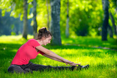 Stretching woman in outdoor sport exercise. Smiling happy doing yoga stretches after running. Fitness model outside in park at summer day stock photos