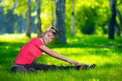 Stretching woman in outdoor sport exercise. Smiling happy doing yoga stretches after running. Fitness model outside in park at summer day royalty free stock photo