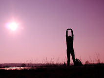 Stretching woman. Silhouette of woman stretching in the sun Stock Photo
