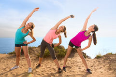 Stretching women outdoors on hike hill near ocean overlooking beach reach toward the sky Royalty Free Stock Photo