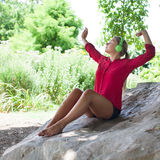 Stretching young girl with headphones enjoying music in city park. Outdoors music - cool suntanned 20s woman stretching in listening to music with earphones Royalty Free Stock Photo
