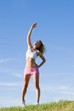 Stretching young sportive woman meadows sunny day Royalty Free Stock Image