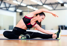 Stretching young woman with earphones in the gym Royalty Free Stock Photos
