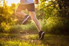 Stretchng sportif de jeune homme avant course dans le jeune homme natureAthletic courant en nature Photos libres de droits