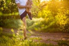 Stretchng sportif de jeune homme avant course en nature Image libre de droits