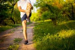 Stretchng sportif de jeune homme avant course en nature Photos stock
