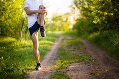 Stretchng sportif de jeune homme avant course en nature Photographie stock libre de droits