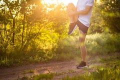 Stretchng sportif de jeune homme avant course en nature Photographie stock