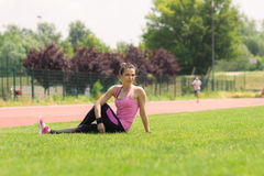 Stretchnig de la muchacha del atleta de lado Imagenes de archivo