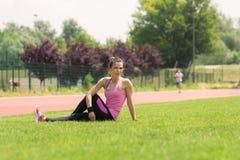 Stretchnig della ragazza dell'atleta lateralmente Immagini Stock