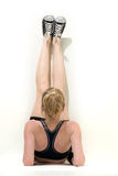 Strething out. Caucasian blond woman with legs up against the wall stretching wearing fitness attire royalty free stock photo