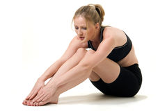 Strething out. Attractive blond caucasian woman stretching before a workout wearing workout attire and bare feet royalty free stock photography