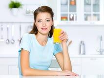 Stretta della ragazza un vetro del succo di arancia fresco Immagine Stock Libera da Diritti