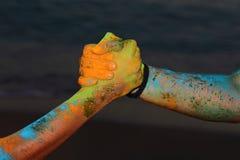 Stretta di mano colorata con la pittura di holi Immagini Stock