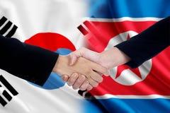 Stretta di mano dei lavoratori con due bandiere coreane Fotografie Stock Libere da Diritti