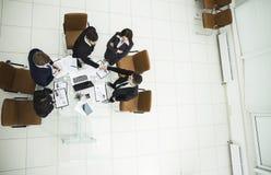 stretta di mano dei soci commerciali prima dei colloqui vicino al desktop dentro Immagini Stock