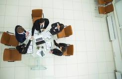 stretta di mano dei soci commerciali prima dei colloqui vicino al desktop dentro Fotografia Stock