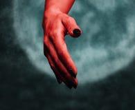 Stretta di mano del demone su fondo della luna Fotografia Stock