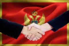 Stretta di mano di cooperazione con la bandiera del Montenegro Fotografia Stock Libera da Diritti
