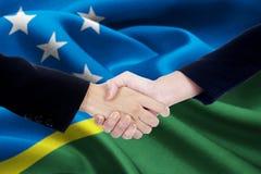 Stretta di mano di cooperazione con la bandiera di Solomon Islands Immagini Stock