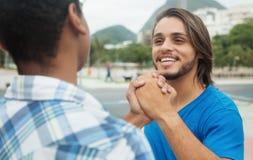 Stretta di mano di un uomo caucasico con l'amico afroamericano Fotografia Stock