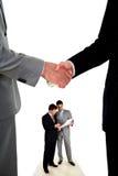 Stretta di mano e due uomini d'affari lavoranti Fotografie Stock Libere da Diritti
