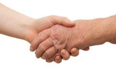 Stretta di mano - fra le giovani e femmine anziane Immagini Stock