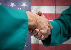 Stretta di mano per la festa dell'indipendenza contro il fondo della bandiera americana Fotografie Stock