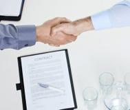Stretta di mano sopra il contratto sulla tabella Immagine Stock