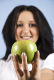 Stretta femminile della gioventù una mela verde Fotografia Stock
