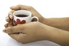 Stretta rossa della tazza di tè in mani Immagini Stock