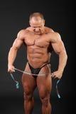 Strette del Bodybuilder che misurano nastro e gli sguardi giù fotografie stock