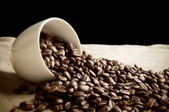 Strewn beans of coffee from a cup on black and flax Royalty Free Stock Photography