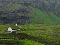 Streymoy, Saksun. View on Saksun`s church and valley. White building with grass roof standing out of the green