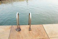 Strichleiter in Swimmingpool Stockbild