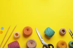 Strickende Faden und nähendes Material auf Farbhintergrund, flache Lage stockfotografie