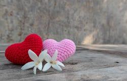 Strickende Herzen mit Millingonia auf Holztisch lizenzfreies stockbild
