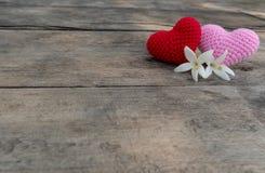Strickende Herzen mit Millingonia auf Holztisch stockfotos