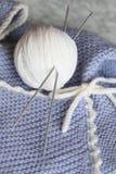 Strickende Wollekugel, Schätzchenüberbrücker und ein Hut Lizenzfreies Stockbild