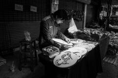 Strickendes Handwerk des Mannes arbeitet auf der Seite der Straße Lizenzfreie Stockbilder