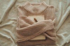 Strickjacke umarmt das Buch Auf der Buchdekoreichel Gelesen, stehen Sie gemütliches Herbst- oder Winterkonzept still stockfotografie